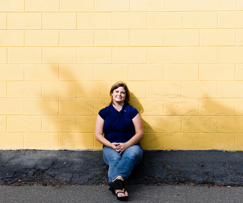 happy woman sitting yellow wall