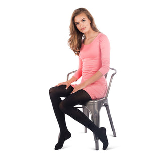 Woman siting on chair wearing black opaque closed toe compression womens pantyhose, 15-20mmHg