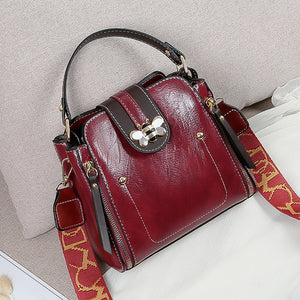 Flap over bumblebee two-toned vegan friendly leather handbag in maroon colour.