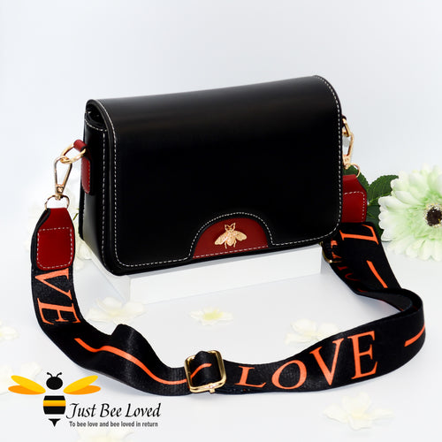 crossbody handbag in black and wine red, featuring a gold bee embellishment, wide matching canvas strap with 'LOVE' text.