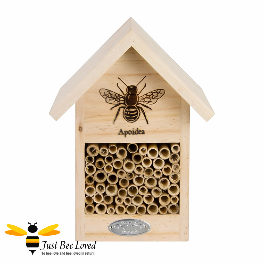 Wooden bee house and hotel featuring wooden tubes and design of a bee on the front.