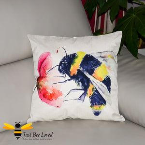 Large scatter cushion with watercolour artwork design of a bumblebee foraging on wild poppy flower