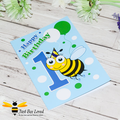 Just Bee Loved Little Bee Happy 1st Birthday for boy greeting card featuring a cute bumble bee with a party hat with the number 1 and balloons design by Artist Yasmin Flemming