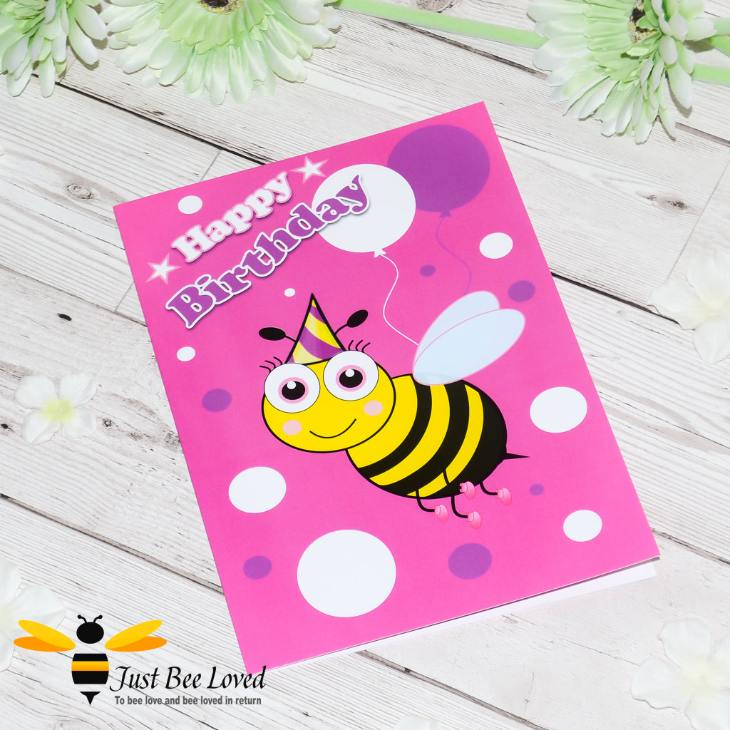 Just Bee Loved Little Bee Happy Birthday Greeting card for Girl featuring bumble bee with a party hat and balloons design by Artist Yasmin Flemming