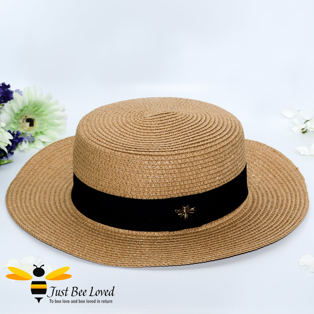 Brown women's straw panama hat with black band and bee embellishment