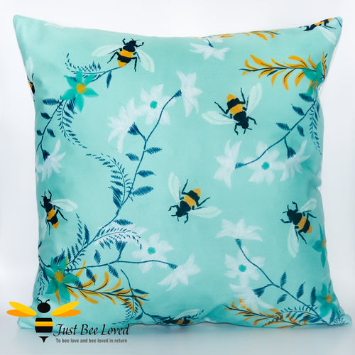 Scatter cushion with embroidered bumblebees in a field of flowers in teal colour.
