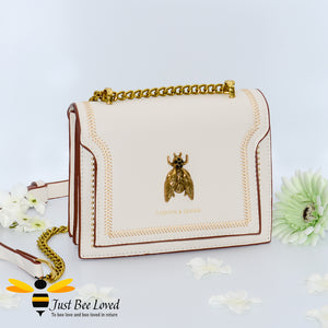 PU leather cream handbag featuring a classic design with large vintage gold bee embellishment, contrasting stitching, gold edged studs with matching strap of part leather and gold chain.