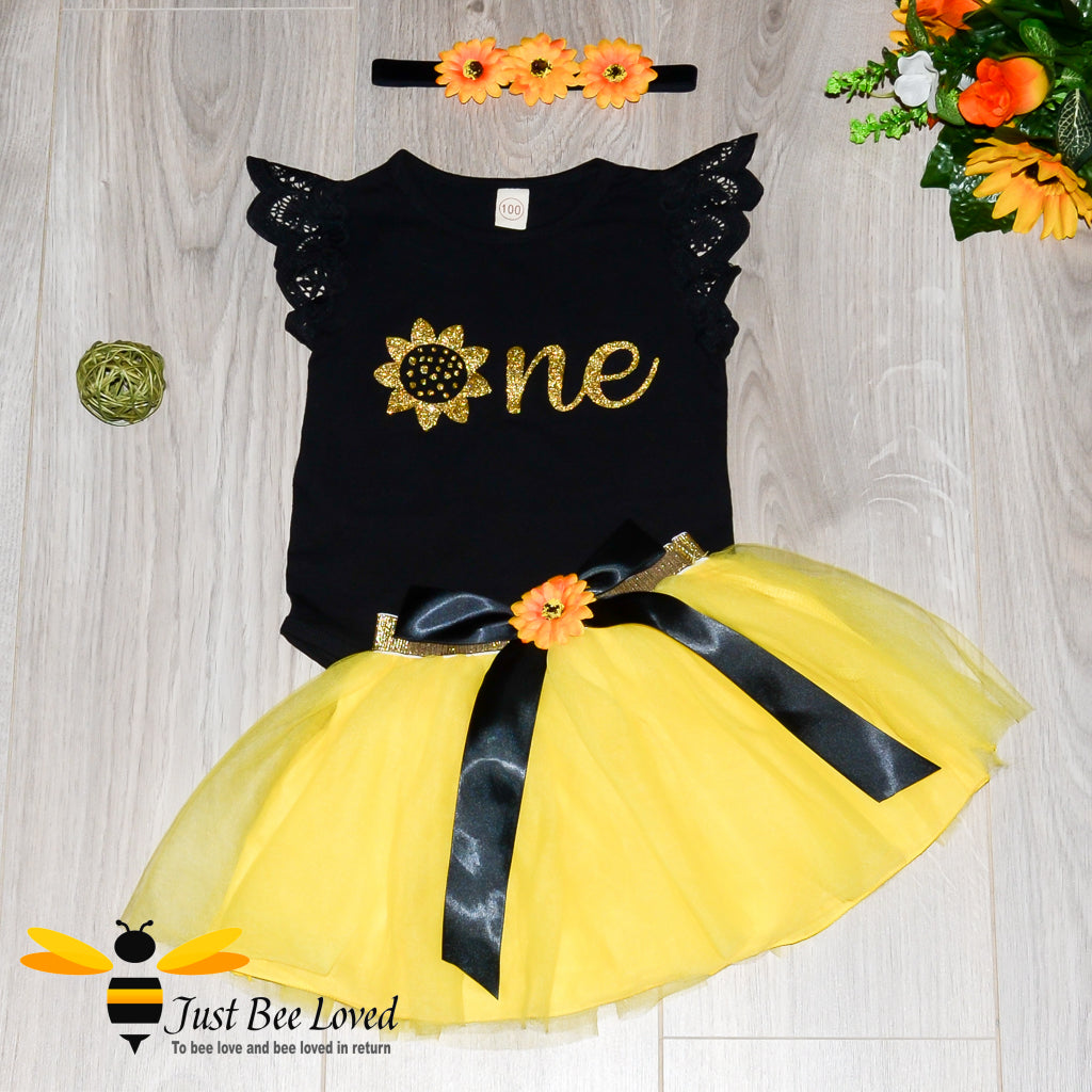 baby girl bee inspired tutu 3-piece party dress. Featuring a black lattice short sleeved romper with a golden sunflower, fully lined yellow tutu skirt and matching sunflower headband.