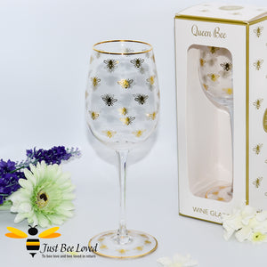 tall stemmed wine glass decorated with golden bees and gold rim