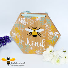 "Load image into Gallery viewer, hexagon shaped wooden hanging plaque with a pictorial message ""Bee Kind"", decorated with painted honeycomb, blue & white leaves with matching blue hanging ribbon."