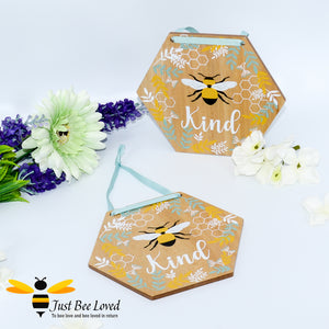 "hexagon shaped wooden hanging plaque with a pictorial message ""Bee Kind"", decorated with painted honeycomb, blue & white leaves with matching blue hanging ribbon."
