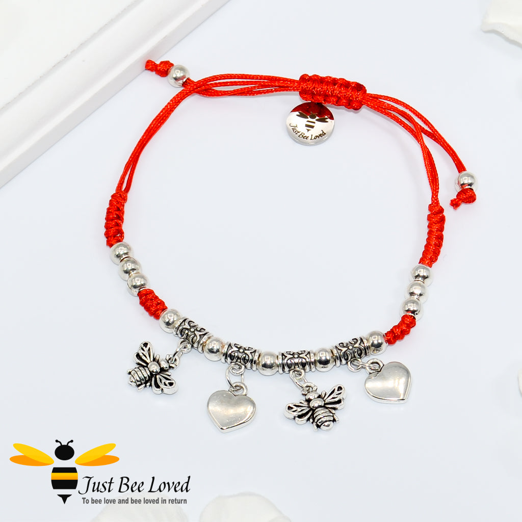 Handmade bohemian gypsy styled red rope bracelet featuring two silver colour bees and two love-heart pendants with beads.