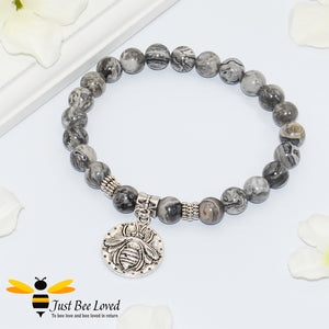 Handmade mottled grey natural stone bead bracelet featuring silver bee charm.
