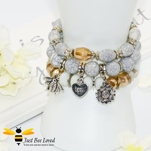 Bohemian gypsy styled 3-layer stack beaded bracelet featuring bee, love-heart and sunflower charms in white, grey and amber