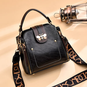 Flap over bumblebee two-toned vegan friendly leather handbag in black.