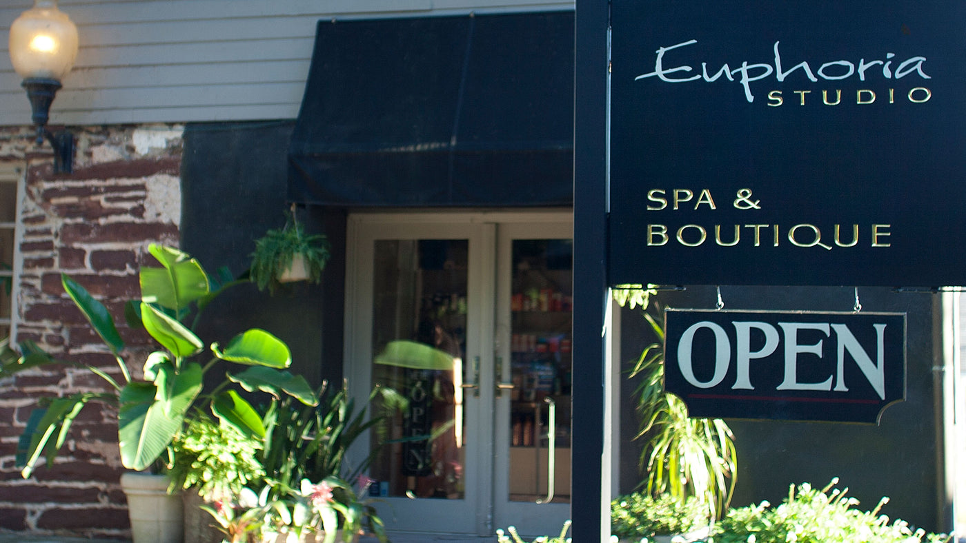 The front of Euphoria Salon, Spa & Boutique in the summer with an open sign.