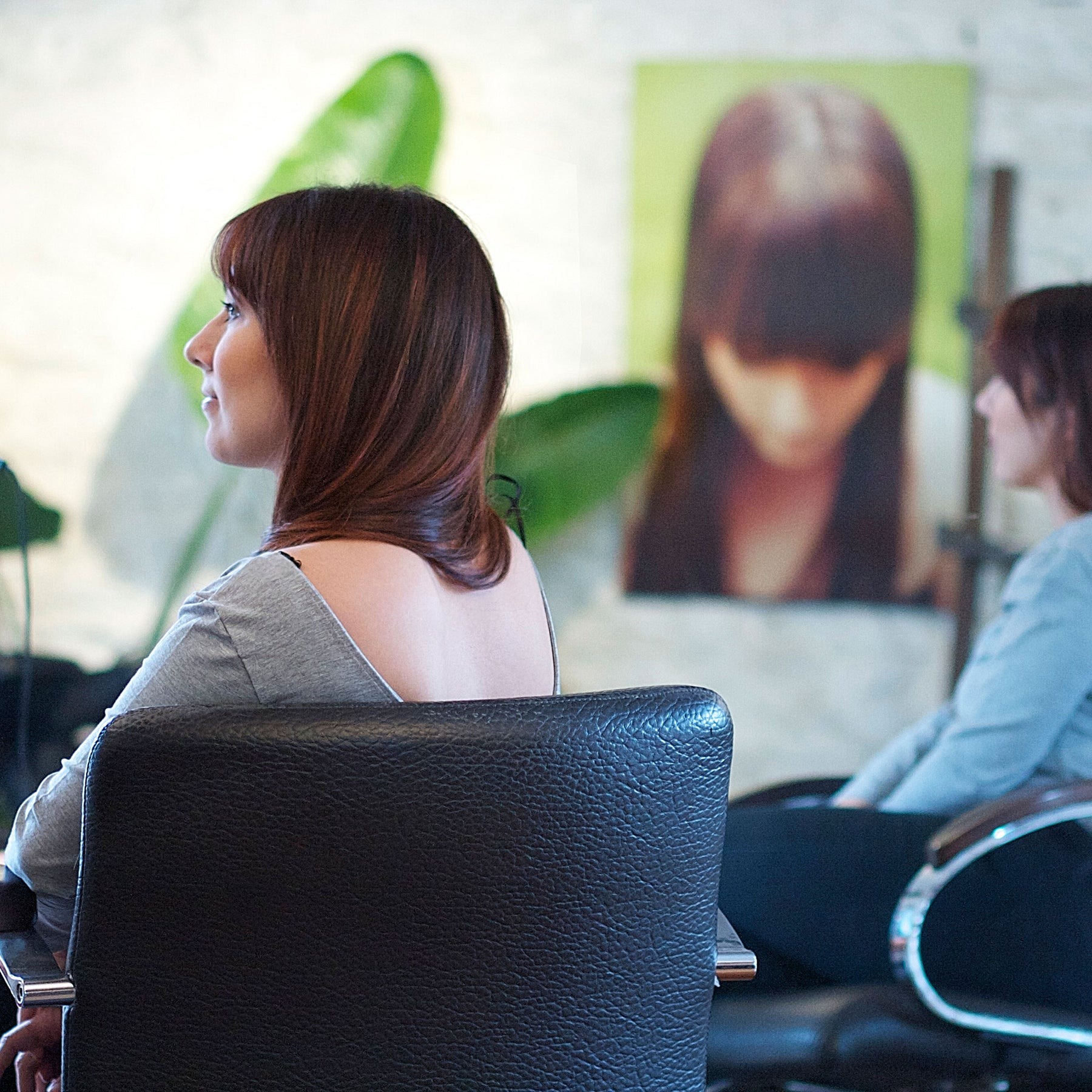 A woman with a beautiful blowout sits in a chair in the Euphoria Salon