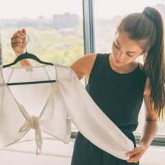 An image of a girl looking at a top on a hanger.