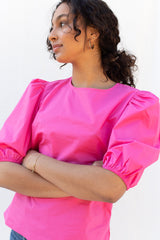 An image of a woman wearing the Azalea Blouse in pink from Beehive.