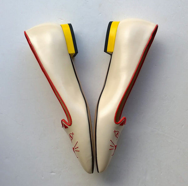 Charlotte Olympia Mid Century Kitty Cream flats with yellow heel and red accent
