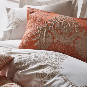 Brick color jacquard shams and white duvet cover decorated with bronze color embroideries