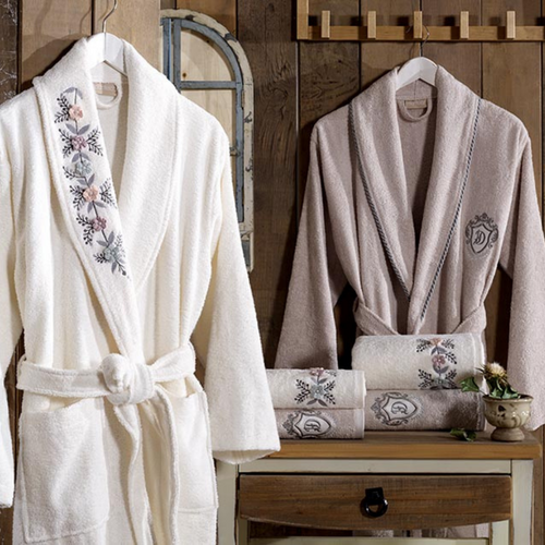 Ecru-cream women`s and stone color men`s bathrobe and towels decorates a bathroom