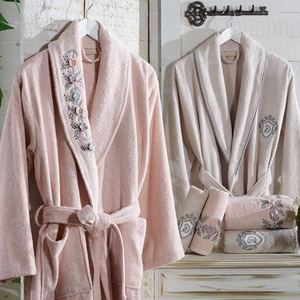 Powder-pink women`s robe and stone color men`s robe in a modern bathroom