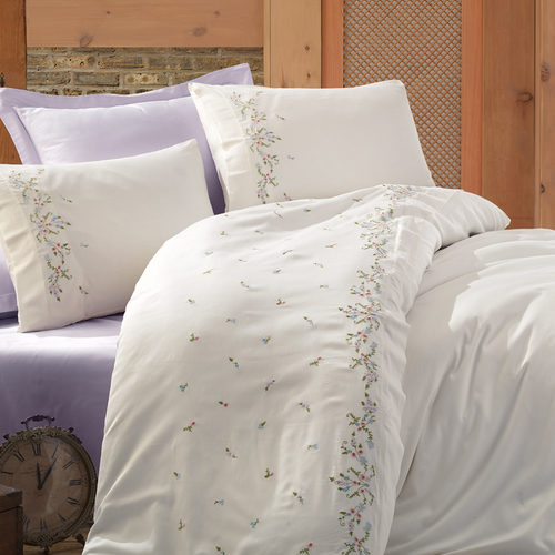 Lilac color bed sheet pairs with white duvet cover that is adorned with colorful floral embroideries
