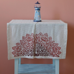 hand-made table runner decorated with red, floral designs