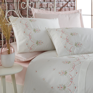Pink, red, green floral embroideries on white duvet cover makes harmony with powder-pink bed sheet  on a white bed