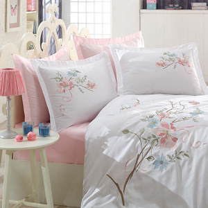 White master bed designed with pink bed sheet and white duvet cover having floral embroideries