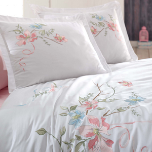 Pink and blue daffodil flowers are embroidered on white, cotton-sateen duvet cover and pillowcases