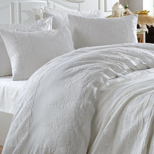 Bride`s bedroom decorated with pure white bedding set ornamented with lace all over the bedspread and duvet cover