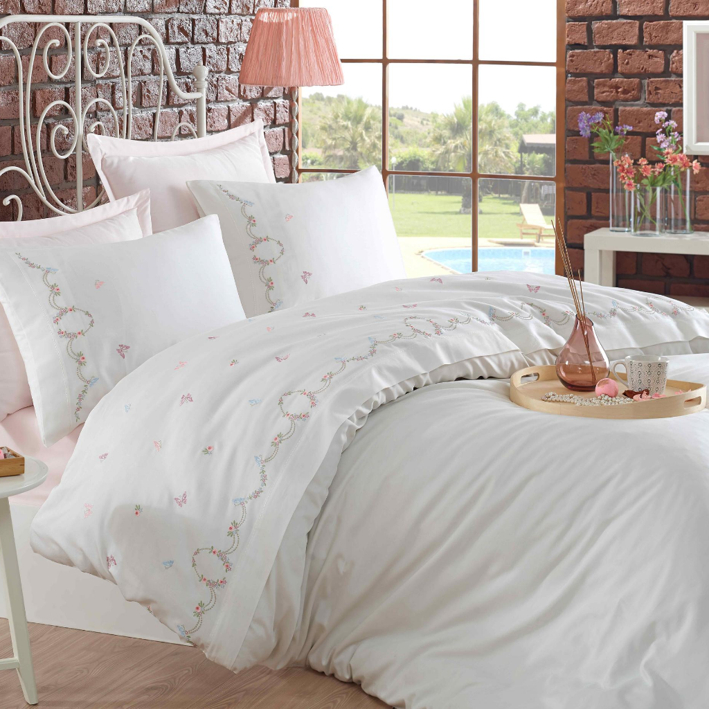 Feminine bedroom with white duvet cover that has pink, green, blue small floral embroideries on it