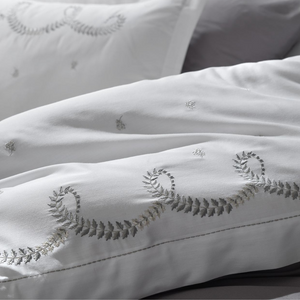 Silver-grey embroideries on white duvet cover and pillowcases combines with grey bed sheet.