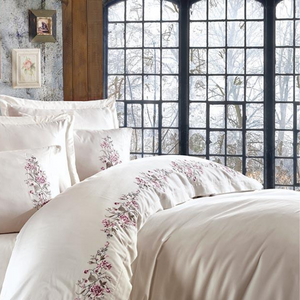 Modern interior designed with creme quilt cover and pillows, decorated with floral ornaments.
