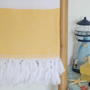 turkish towel in yellow color has hand tied tassels