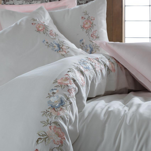White duvet cover is adorned with pink, green and blue floral embrioderies and pairs with pink bed sheet and pillowcases