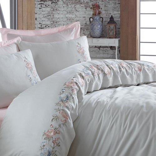Modern bedroom is decorated with white and pink, cotton-sateen bed linen.