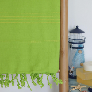 Green towel made of Turkish cotton has hand-tied tassels at borders