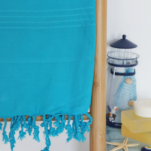Blue, cotton beach towel has hand-tied tassels