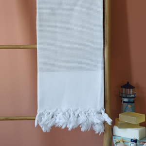 Peshtemal towel has grey stripes and white hand-tied tassels