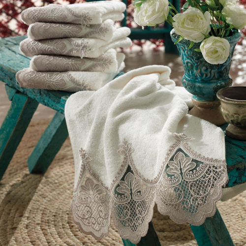 Luxurious room designed with a green table,  flowers and ecru color Turkish hand towels which are ornamented with bronze color French lace