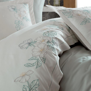 Green and grey floral embroideries on white bed cover and pillows
