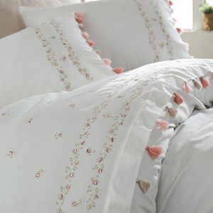 White duvet cover and pillows decorated with pink and beige tassels and floral embroideries