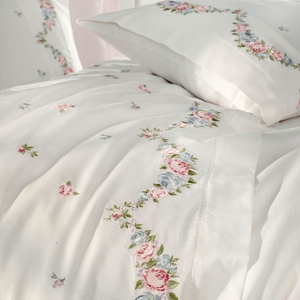 Pink, blue, green floral embroideries on white duvet cover makes a combination with pink bed sheet