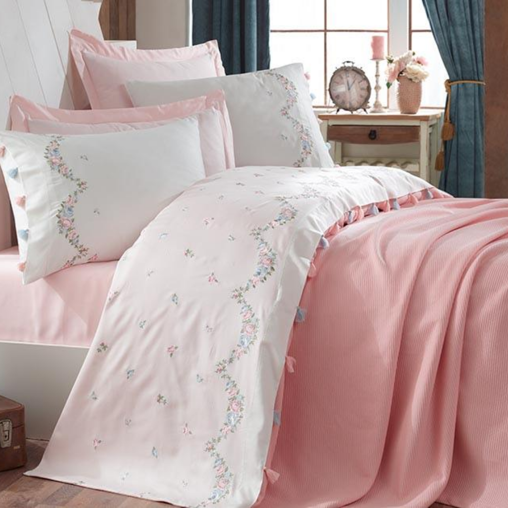 Romantic bedroom decorated with pink, cotton bed linen and blanket