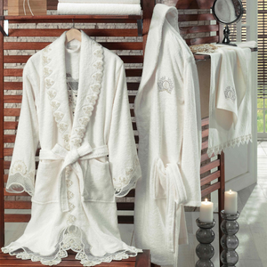 Romantic bathroom decorated with candles and bathrobe which has heart-shaped guipure and lace ornaments