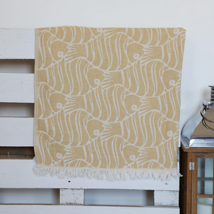 Mustard color, soft Turkish beach towel has fish designs