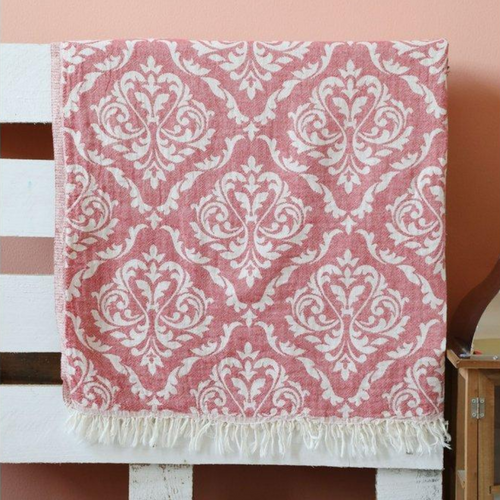 Red Oriental Turkish peshtemal towel hanging on the bed frame